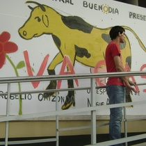 Rogelio Orizondo in front of the advertisement for the theatrical production, Vacas
