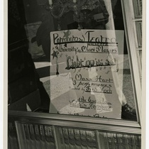 Photograph of store window sign announcing the theatrical production, Light Up the Sky